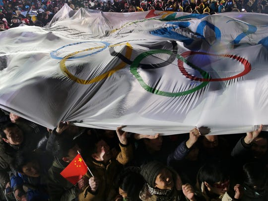 Chinese people hold a giant banner with the logo for