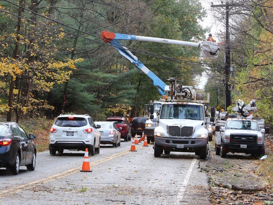 Workers fix a power line on Route 202 near Wilder Road