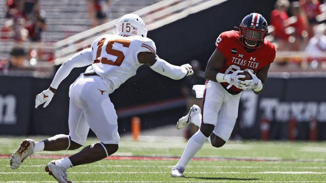 Texas Tech receiver KeSean Carter (82) looks for running room as Texas safety Chris Brown closes in on during Saturday's Big 12 opener at Jones AT&T Stadium. Carter caught Tech's first two touchdown passes, but the Red Raiders lost 63-56 in overtime.