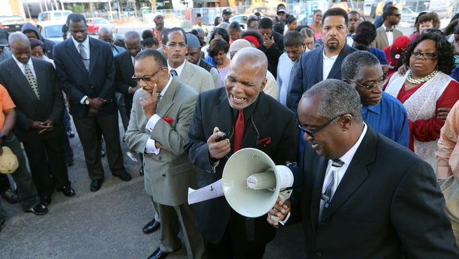 Rev. Artis White  leads a group in prayer during a vigil at the site of a drive-by shooting on Genesee Street that left three dead and four injured.
