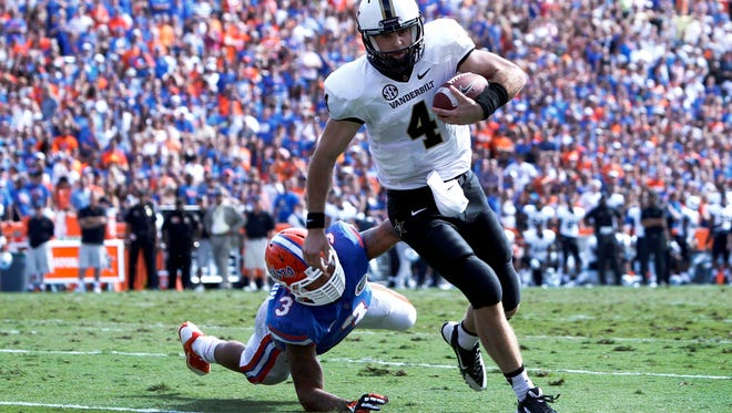 Vanderbilt quarterback Patton Robinette (4) breaks the tackle of Florida's Antonio Morrison (3) and takes it in for a second-quarter TD.
