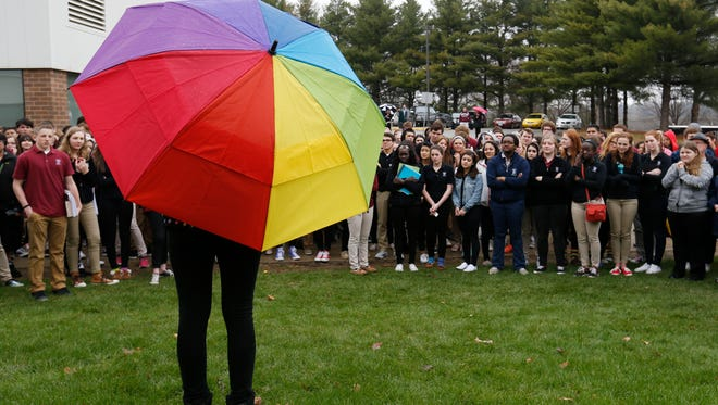 Dowling Catholic freshman Saffron Edwards, 15 (center), speaks to the crowd from under her rainbow-colored umbrella Wednesday, April 8, 2015, during a walkout protesting the private Catholic school's decision not to hire a gay teacher in Des Moines. More than 150 students, alumni and supporters gathered outside the school to protest the school's decision.