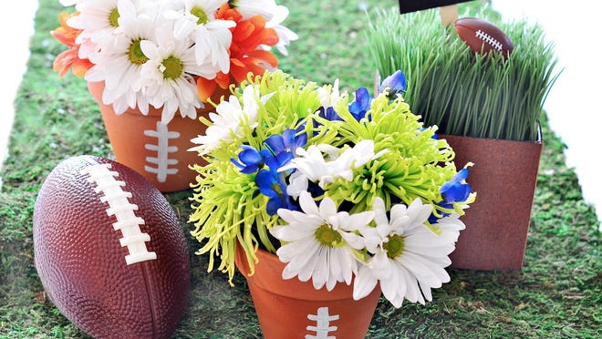 """Craft a centerpiece from inexpensive clay pots painted with white """"football laces"""" lines and filled with grocery-store flowers."""