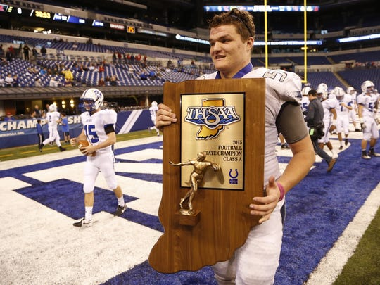 FILE - Coy Cronk carries the Class A state title trophy off the field after Central Catholic defeated Linton-Stockton 34-7 in the finals Nov. 27, 2015, at Lucas Oil Stadium.