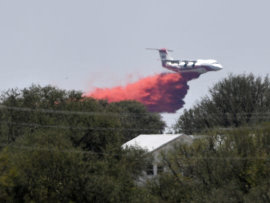 A Texas A&M Forest Service tanker drops fire retardant south of Zephyr Tuesday.