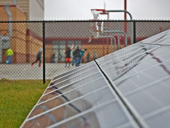 Solar panels work sit positioned next to a playground