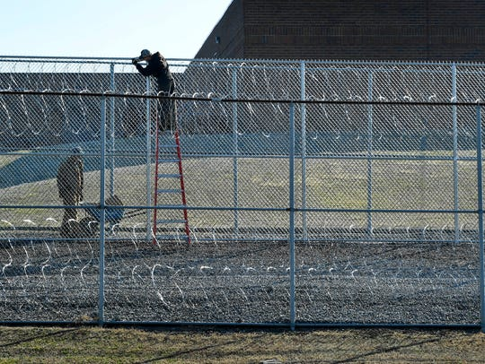 Workers repair the razor wire around the Tennessee