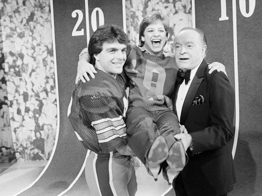 Heisman Trophy winner Doug Flutie and comedian Bob Hope hoist gymnast Mary Lou Retton in 1984.