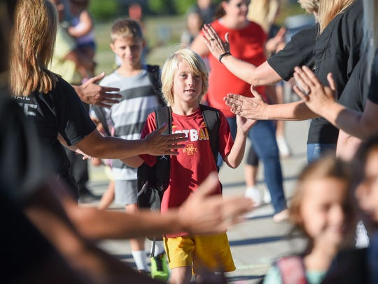 Fourth-grader Kobe Beherns high fives teachers on his way into school on Wednesday, Aug. 23, 2017, during the first day of school at Prairie Trail Elementary.