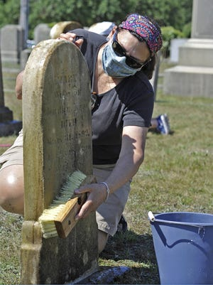 Terry Somerson washes down one of the headstones at Beech Grove Cemetery on Main Road in Westport during the regular Saturday morning cleanup held by the Westport Historical Society.