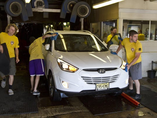 Car wash attendants begin the drying process on a car emerging from the wash at Butch's Lube 'N Wash in Red Bank.