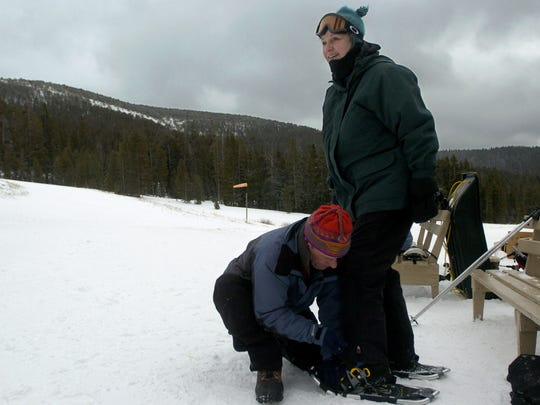 Matt Marcinek, left, of Montana State Parks, helps first time snowshoer Margaret Onstad strap in to her snowshoes at Winter Trails Day.