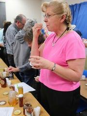 Debbie Spangler of Sheboygan tastes honey during the