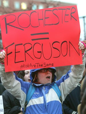 Neka Zimmerman, of Rochester, holds a sign as part a protest at UR against the decision to not charge the police officer in Ferguson in the shooting death of Mike Brown.