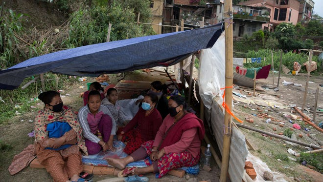 A Nepalese family gathers in a shelter in Kathmandu on April 29, 2015.