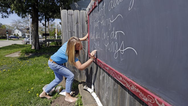 Brenda Arts writes an inspirational quote on the chalkboard outside her house in Appleton.
