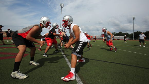 Players run drills on the first official day of football