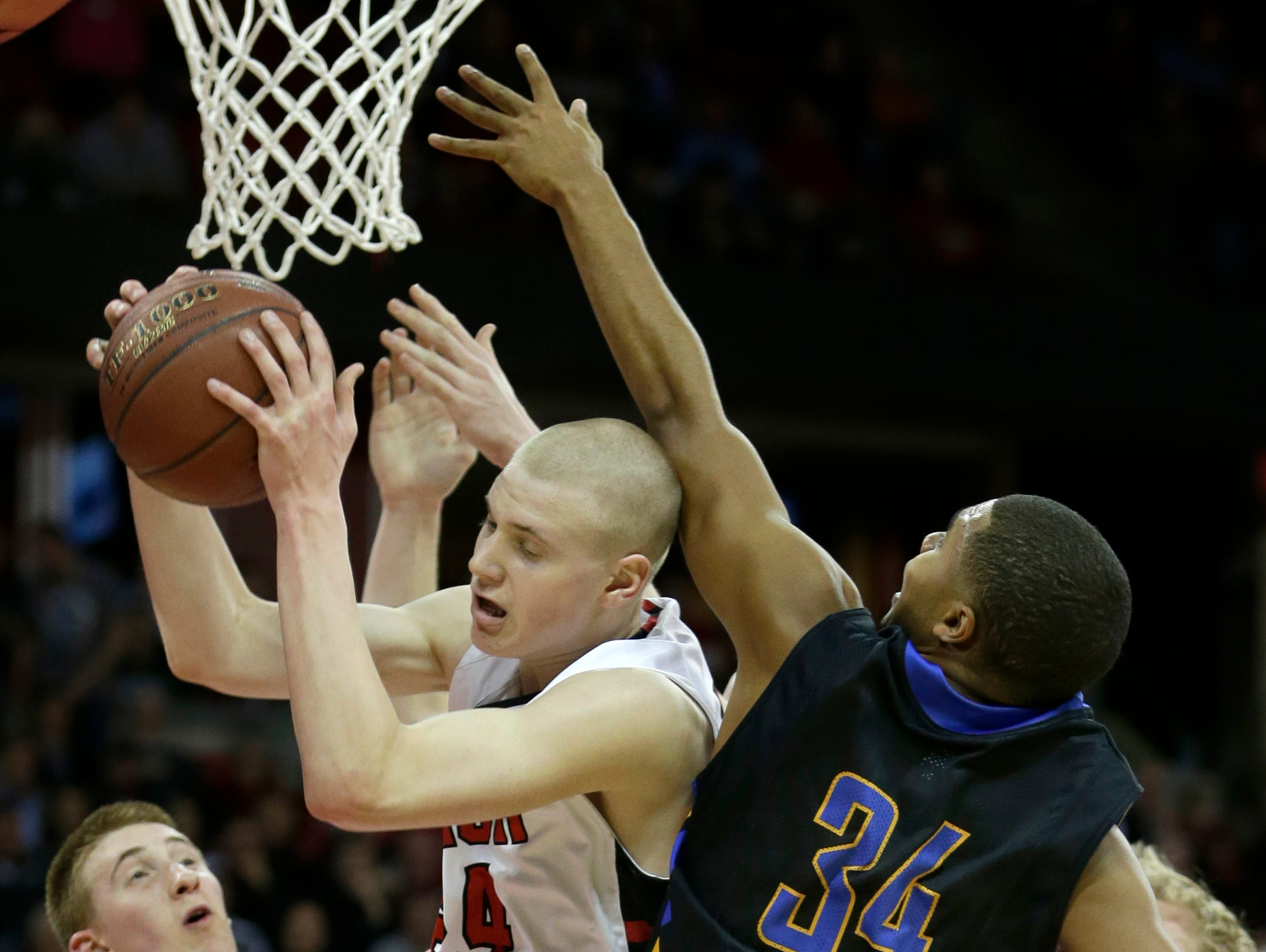 SPASH's (center) Joey Hauser and Germantown's Dwayne Lawhorn Jr. battle for a rebound during Saturday's WIAA Divsion 1 boys' state basketball championship at the Kohl Center in Madison.
