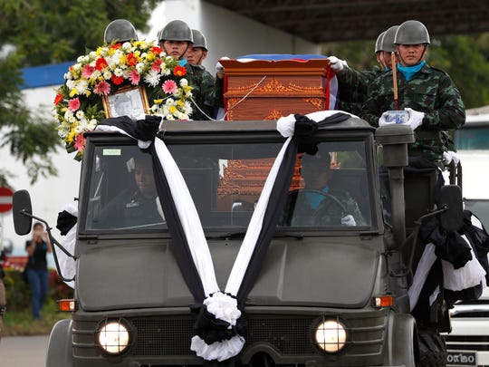 Thai military honor guards transport a coffin containing