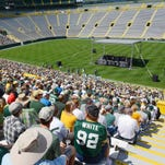 Two of the estimated more than 20,000 shareholders listen to the executive presentation during the 2006 shareholders meeting at Lambeau Field in Green Bay.
