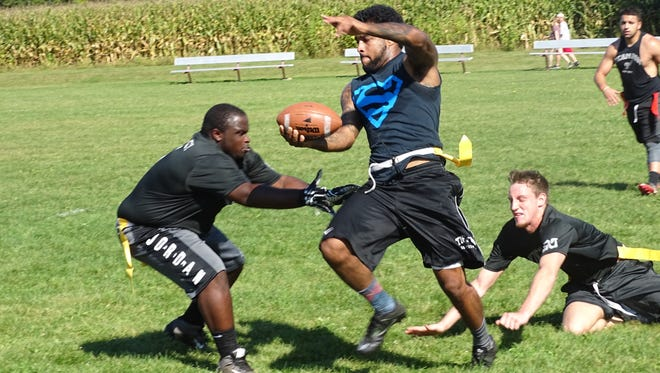 Roughriders quarterback Jaquan Ransome attempts to elude King Slayers defenders Jake Grigsby, right, and Dakota Pressley on Sunday during a Mid-State Flag Football League game at Evans Park in Hebron.
