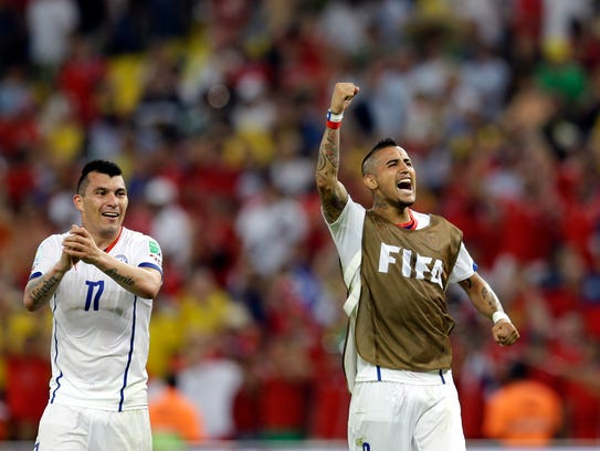 Chile's Arturo Vidal, right, and Chile's Gary Medel celebrate after their victory in the group B World Cup soccer match between Spain and Chile at the Maracana Stadium in Rio de Janeiro, Brazil, Wednesday, June 18, 2014. Defending champion Spain was eliminated from the World Cup after losing to Chile 2-0. (AP Photo/Natacha Pisarenko)