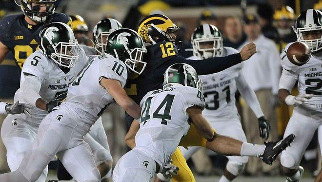 Michigan punter Blake O'Neill loses the ball under pressure from Michigan State's Grayson Miller, Matt Morrissey and Andrew Dowell.