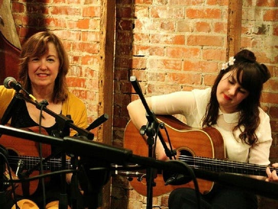 Jane Vidrine, left, plays guitar with her daughter