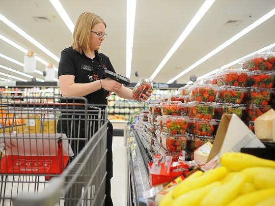 Kelsey Wagner, Aisles Online manager, scans a package of strawberries while shopping for an Aisles Online customer Thursday, Feb. 25, 2016, at the Hy-Vee location on South Minnesota Avenue in Sioux Falls.