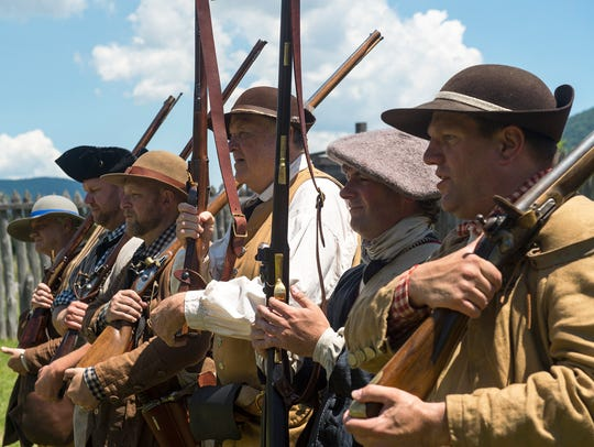 Re-enactors, as associators, stand in formation at