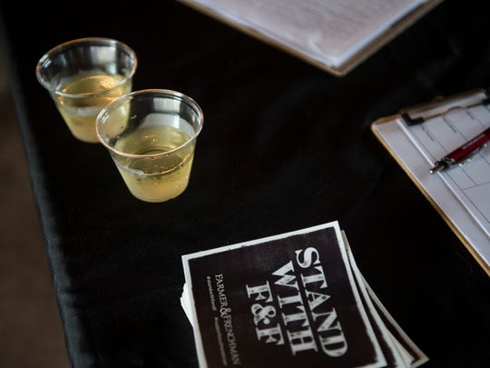 """Wine glasses sit next to the petition to keep the area """"wet"""" at Farmer & Frenchman Winery on Thursday, June 7, 2018."""