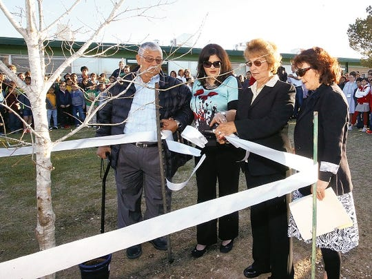 Trish Adams, right, counselor at Putnam Elementary School, watches as Linda De La Cruz cuts a ribbon dedicating a red oak tree to her late son, Constable Robert White, at the West Side school in 2015. He had worked as a coach for more than 15 years at Putnam Elementary.