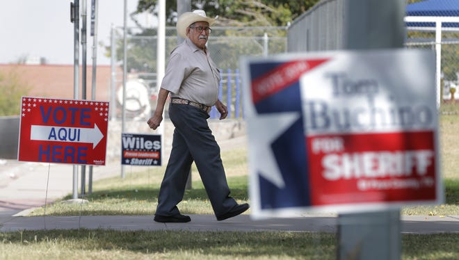 Voters walk past campaign signs on their way to vote at Pavo Real Recreation Center in the lower valley. Record numbers of voters continue to flood the polls in El Paso.