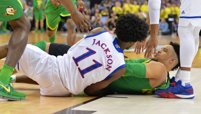 Kansas Jayhawks guard Josh Jackson (11) and Oregon Ducks forward Dillon Brooks (24) on the court during the first half in the finals of the Midwest Regional of the 2017 NCAA Tournament at Sprint Center.