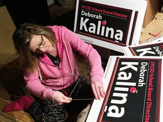 Deborah Kalina assembles lawn signs at her Codorus