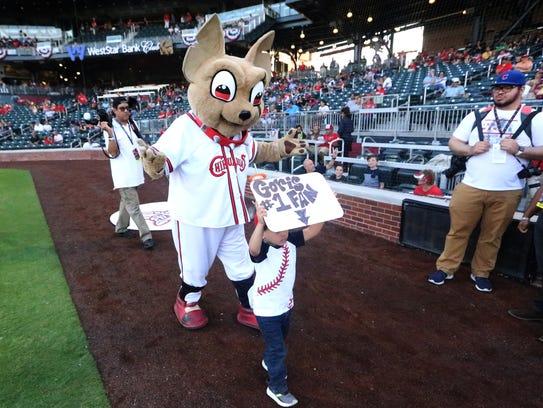 Chico the El Paso Chihuahuas mascot leads a small boy