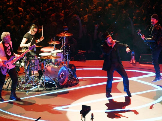 U2, with singer Bono, front, in top hat and white makeup