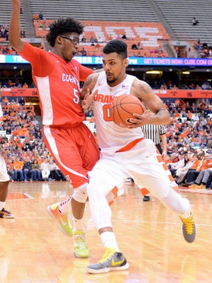 Syracuse Orange guard Michael Gbinije drives the ball and is pressured by Cornell Big Red guard Robert Hatter  during the second half of a game at the Carrier Dome. Syracuse won 67-46.