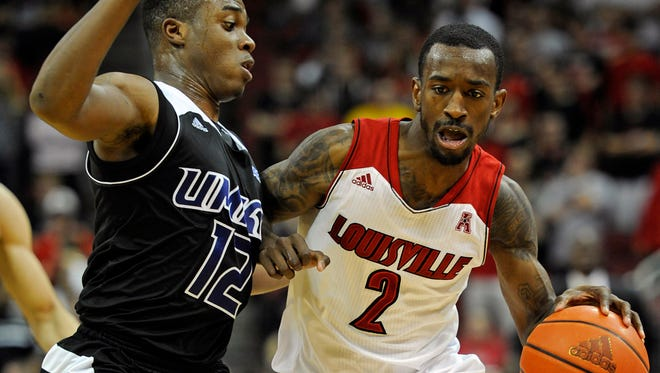 Louisville Cardinals guard Russ Smith dribbles against UKMC Kangaroos guard Martez Harrison during the second half at the KFC Yum! Center.