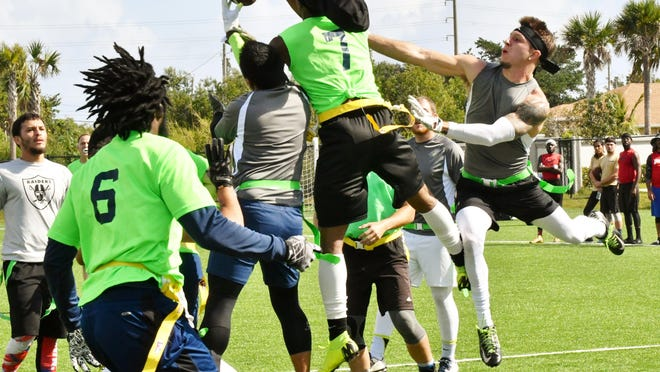 A Seahawks player comes up with an interception in the end zone during their victory over the Saints in Fun Sports, Inc.'s flag football action Sunday at SLAM! charter school in West Palm Beach.