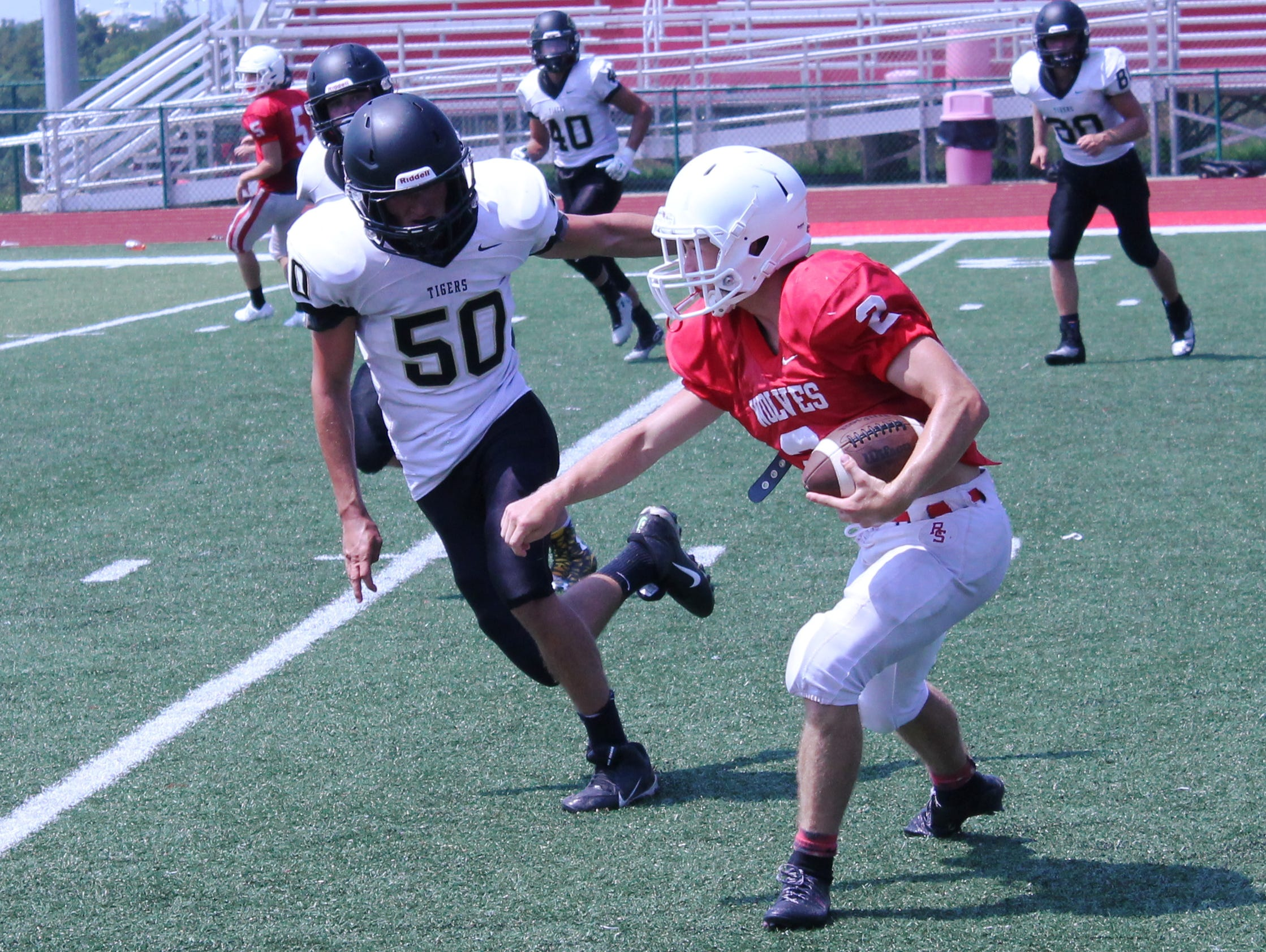 Reeds Spring wide receiver Joel Gertson (right) gains yards after the catch against the Versailles defense during a football scrimmage at the 2016 Branson Team Camp at Pirate Stadium.
