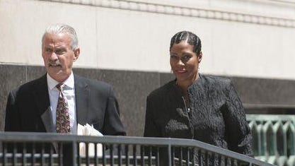 Monica Morgan-Holiefield, right, and defense lawyer Steve Fishman, left, leave federal court during a recent hearing.