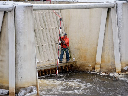 St. Cloud Hydroelectric Dam Plant Supervisor Daryl Stang uses a long pole and air pressure to clean the trash racks leading into generating unit one Wednesday, Dec. 2. Debris flowing down river collects in the racks and needs to be removed to keep water flowing smoothly into the generators.