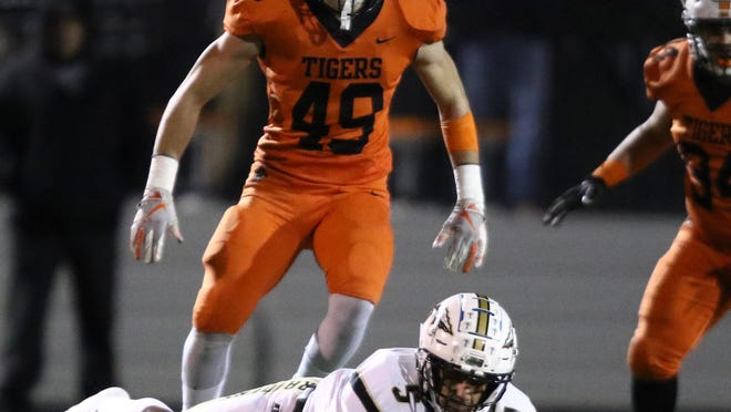 Massillon's Caiden Woullard (49) stands over Warren Harding's Elijah Taylor after a play during the Tigers' opening-round playoff win over the Raiders in 2019.
