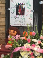Flowers and stuffed animals help make up a memorial