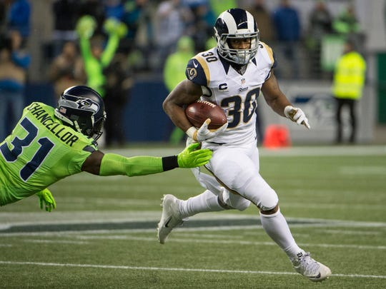 Los Angeles Rams running back Todd Gurley (30) runs past Seattle Seahawks strong safety Kam Chancellor (31) at CenturyLink Field.