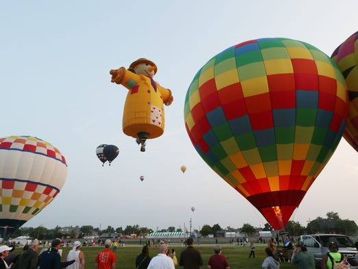 Balloons come to life in the infield of the Indiana State Fairgrounds just after sunrise for the start of the annual balloon race Friday, August 1, 2014.