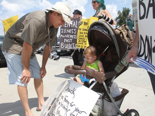Scott Youngkin greets Hyacinth Michaels, 14 mos., during a protest of the misdemeanor charge for Officer Jason Shuck in front of the Greene County Courthouse on Tuesday, August 26, 2014. Protesters said that the third-degree assault charge is too lenient.
