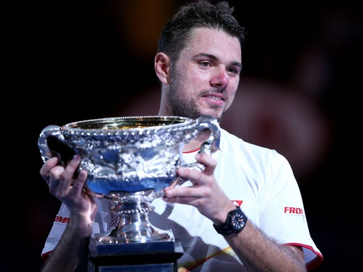 Stanislas Wawrinka poses for pictures with his first career Grand Slam trophy after defeating Rafael Nadal at the Australian Open.