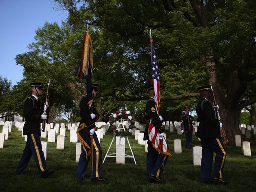 A U.S. military honor guard walks past the grave of U.S. Army Pvt. William Christman after a wreath-laying ceremony May 13 at Arlington National Cemetery. The 624-acre national cemetery is commemorating its 150th anniversary and Christman was the first military member to be buried there.